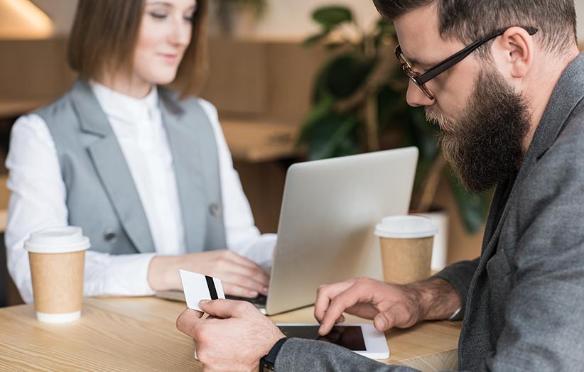 Frau und Mann arbeiten an Laptop und Smartphone.